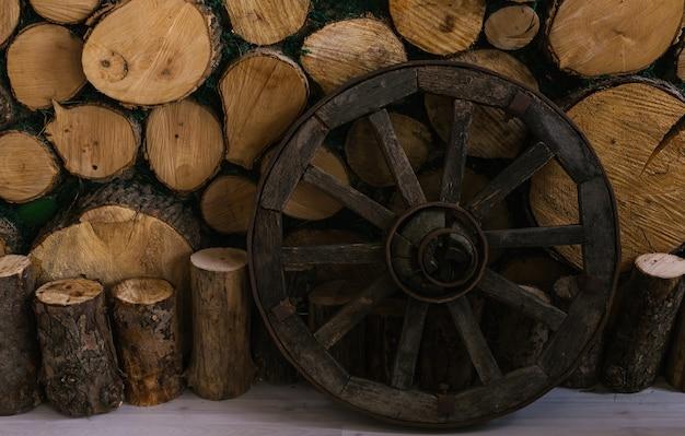 Uma roda de madeira fica perto de uma parede de troncos.