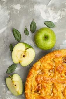 Uma rodada de bolo de maçã com vista de cima formou-se deliciosamente com farinha de maçã fresca na massa de bolo de mesa branca