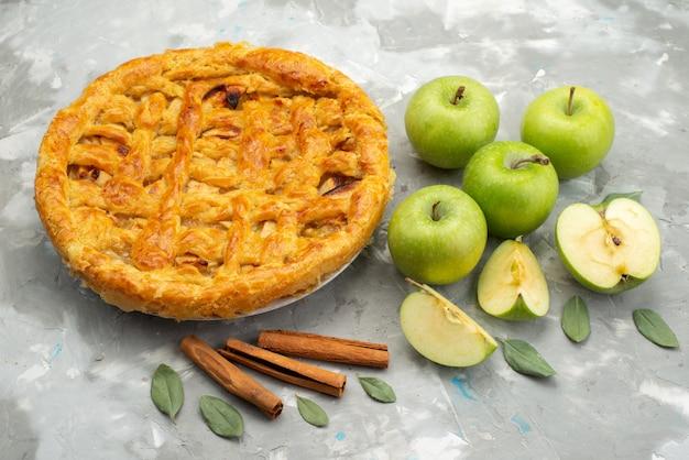 Uma rodada de bolo de maçã com vista de cima formou-se deliciosamente com maçãs frescas na mesa branca.