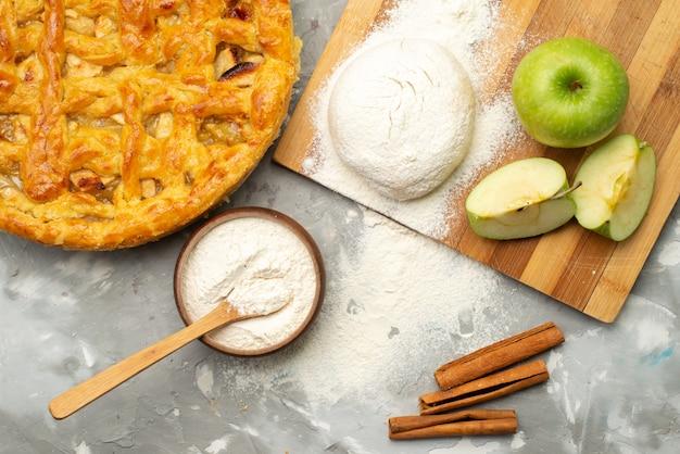 Uma rodada de bolo de maçã com vista superior formou-se deliciosamente com farinha de maçã fresca no biscoito de mesa branco