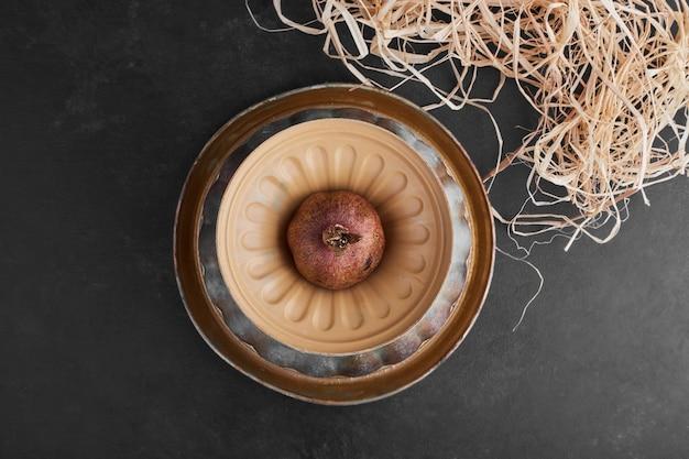 Uma romã em uma tigela de cerâmica.