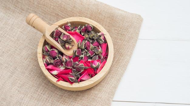 Uma rosa seca do rosa do chá em uma tabela de madeira branca.