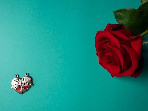 Uma rosa vermelha com pétalas verdes que fica de lado e duas partes de um coração de prata com uma inscrição em verde