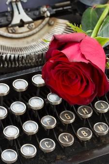 Uma rosa vermelha em uma máquina de escrever vintage close-up