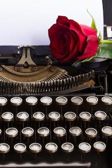 Uma rosa vermelha em uma máquina de escrever vintage com página em branco