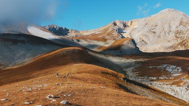 Uma rota através de picos e colinas através de paisagens majestosas com turistas e viajantes à distância.