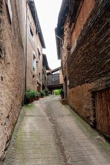 Uma rua estreita de casas antigas construídas com lajes de adobe