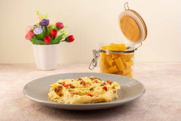 Uma saborosa refeição de massa italiana com vegetais cozidos e pequenas fatias de carne dentro de um prato cinza junto com flores e massa crua em rosa