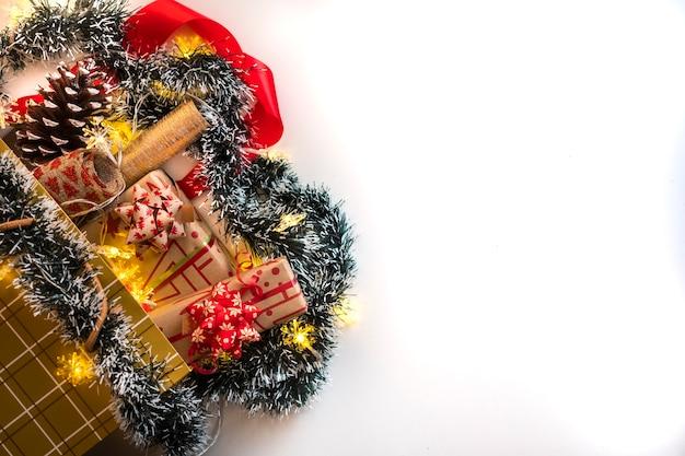 Uma sacola de compras dourada com presentes de natal e enfeites em um fundo branco iluminado