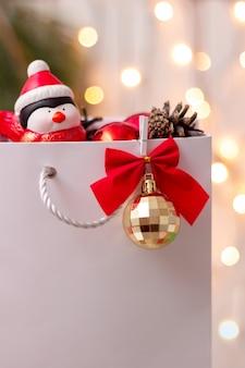 Uma sacola de papel branco com uma bola dourada, um laço vermelho com um galho de árvore de natal e um pinguim de brinquedo
