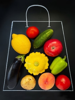Uma sacola de supermercado desenhada com giz em um fundo preto cheia de vegetais e frutas