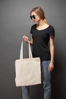 Uma sacola ecológica para maquete é segurada por uma mulher sobre uma textura cinza