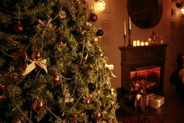 Uma sala de natal iluminada apenas pelo fogo e pela árvore de natal