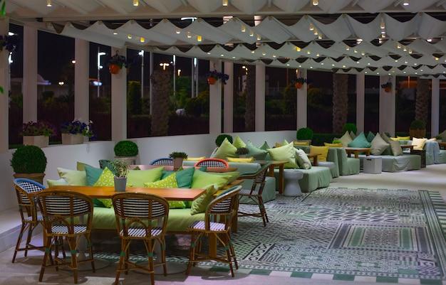 Uma sala de restaurante com móveis de cores vivas e janelas panorâmicas.
