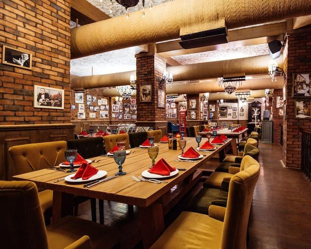 Uma sala de restaurante com paredes de tijolo vermelho, mesas de madeira e canos no teto