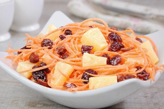 Uma salada de abacaxi, cenoura fresca, cranberries secas, molho de iogurte. vegan sem glúten.
