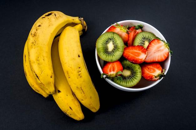 Uma salada de frutas ao lado de um cacho de bananas no preto