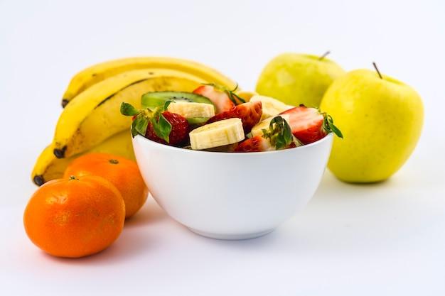Uma salada de frutas cortada em uma tigela branca em branco ao lado de tangerinas, bananas e maçãs