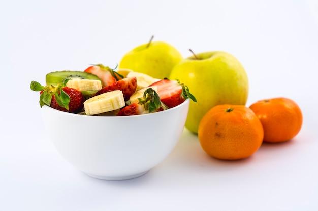 Uma salada de frutas cortada em uma tigela branca em branco ao lado de tangerinas e maçãs