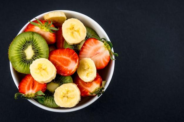 Uma salada de frutas cortada em uma tigela branca no preto