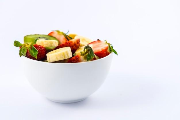 Uma salada de frutas cortada em uma tigela branca, receita agradável e saudável