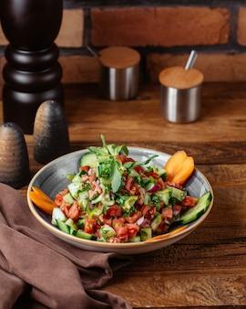 Uma salada de legumes com limão dentro do prato na mesa de madeira marrom