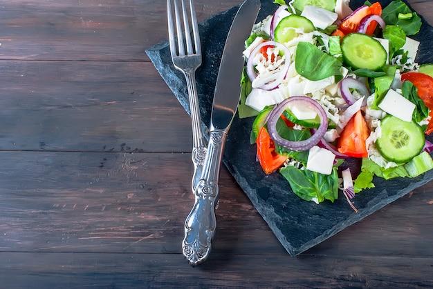 Uma salada misturada com pepino, tomates, queijo macio, espinafres e cebola vermelha.