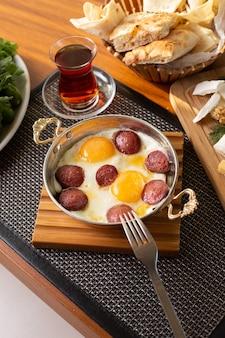 Uma salsicha vista de cima com ovos, chá e pão no café da manhã