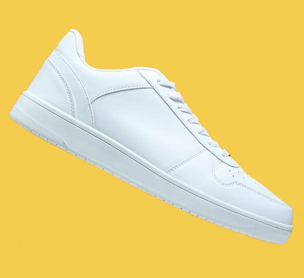 Uma sapatilha branca e isolado no amarelo