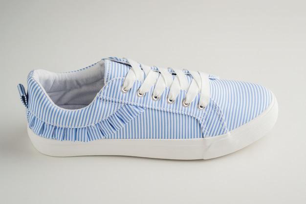 Uma sapatilha feminina listrada azul
