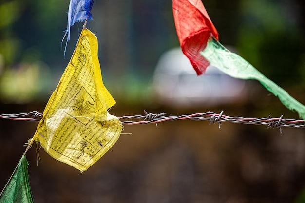 Uma seção da bandeira de mantra com arame farpado e suave desfoque