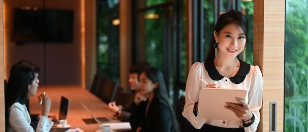 Uma secretária está tomando notas enquanto está em frente a uma sala de reuniões