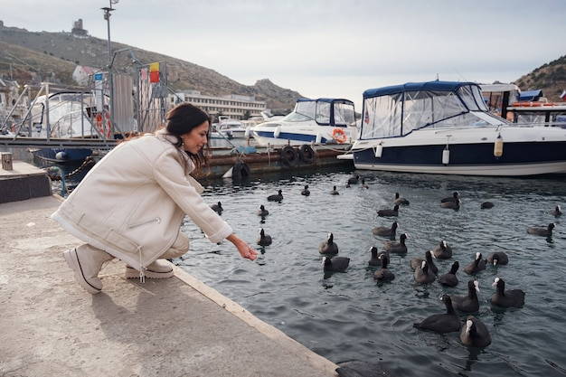 Uma senhora caucasiana despreocupada em roupas bege, apreciando a vista do mar em um dia quente de vento