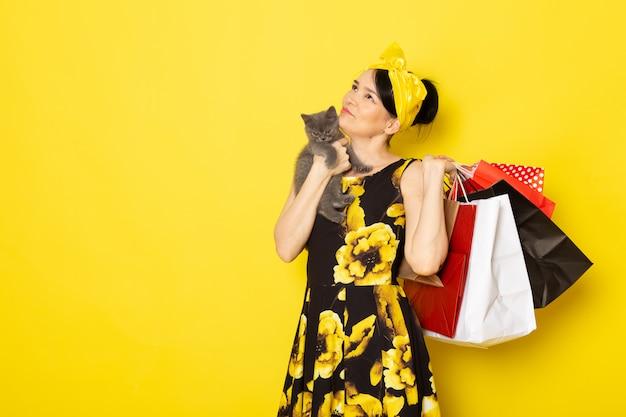 Uma senhora de vista frontal em vestido amarelo-preto flor projetado com bandagem amarela na cabeça segurando pacotes de compras e gatinho no amarelo