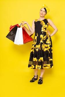 Uma senhora de vista frontal em vestido amarelo-preto flor projetado com bandagem amarela na cabeça segurando pacotes de compras no amarelo