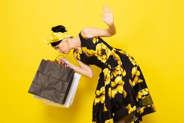 Uma senhora de vista frontal em vestido amarelo-preto flor projetado com bandagem amarela na cabeça segurando pacotes de compras, verificando-os no amarelo