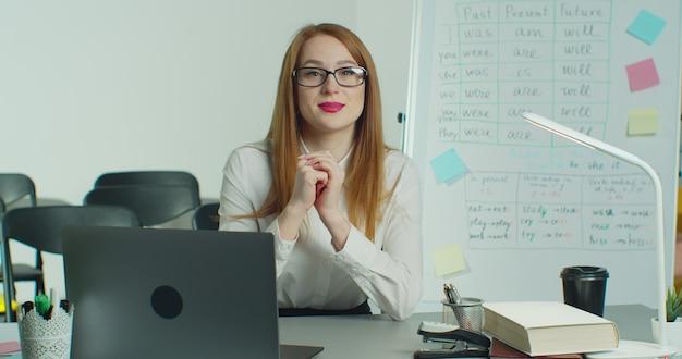 Uma senhora está usando um laptop para dar uma aula online.