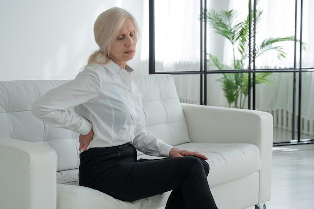 Uma senhora idosa com dores nas costas, uma mulher de meia idade levanta-se do sofá e sente dores nas costas