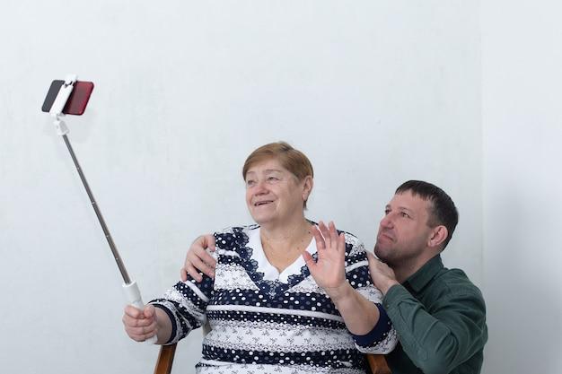 Uma senhora idosa com seu filho falando ao telefone, o bastão de selfie na mão