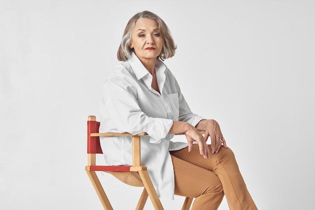 Uma senhora idosa com uma camisa branca sentada numa cadeira a posar