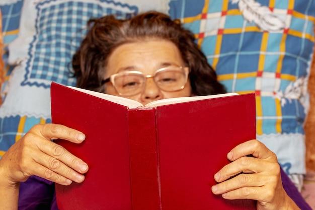 Uma senhora idosa deita no sofá e lê um livro