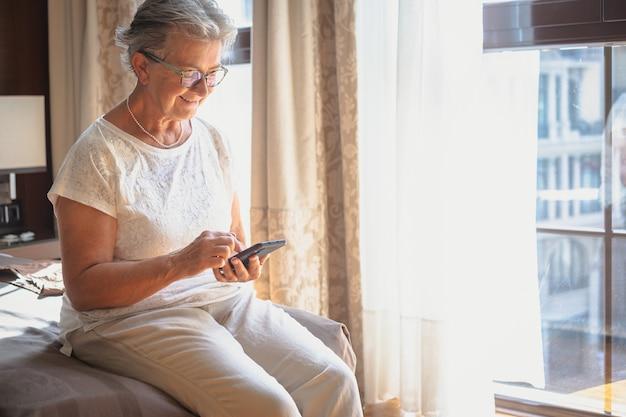 Uma senhora idosa em um quarto de hotel está sentada na cama usando seu telefone celular. uma grande janela atrás dela