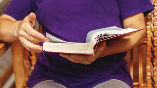 Uma senhora idosa está lendo um livro, segurando-o nas mãos e sentada em uma cadeira. lendo a bíblia