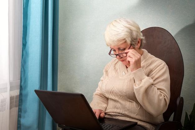 Uma senhora idosa está sentada em casa em uma cadeira com um laptop, segura os óculos e imprime no teclado.