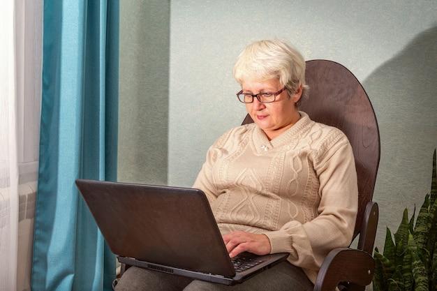 Uma senhora idosa está sentada em casa em uma cadeira com um laptop.