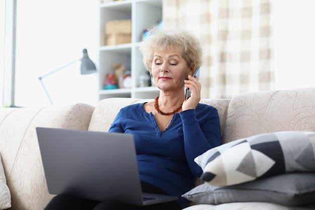 Uma senhora idosa está sentada no sofá com um laptop e smartphone