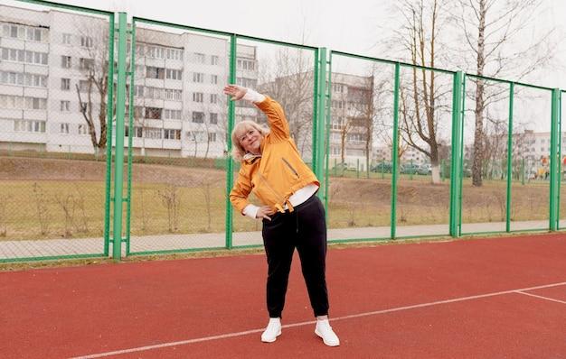 Uma senhora idosa faz exercícios no estádio na esteira vermelha. estilo de vida saudável
