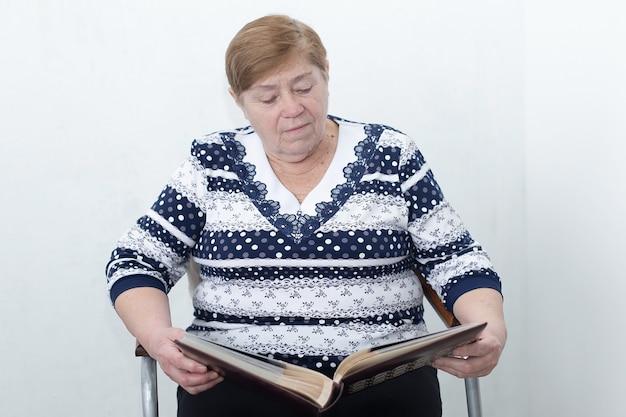 Uma senhora idosa olha um álbum de fotos
