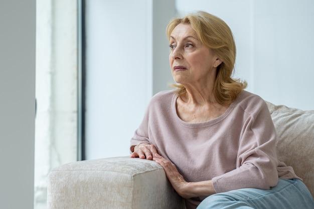 Uma senhora idosa pensativa está sentada no sofá da sala, olhando pela janela para