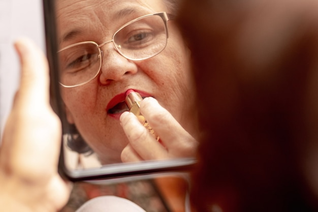 Uma senhora idosa pinta os lábios com batom, cuidando de sua beleza. mulher idosa séria aplicar batom na frente de um espelho. reflexo de uma mulher no espelho